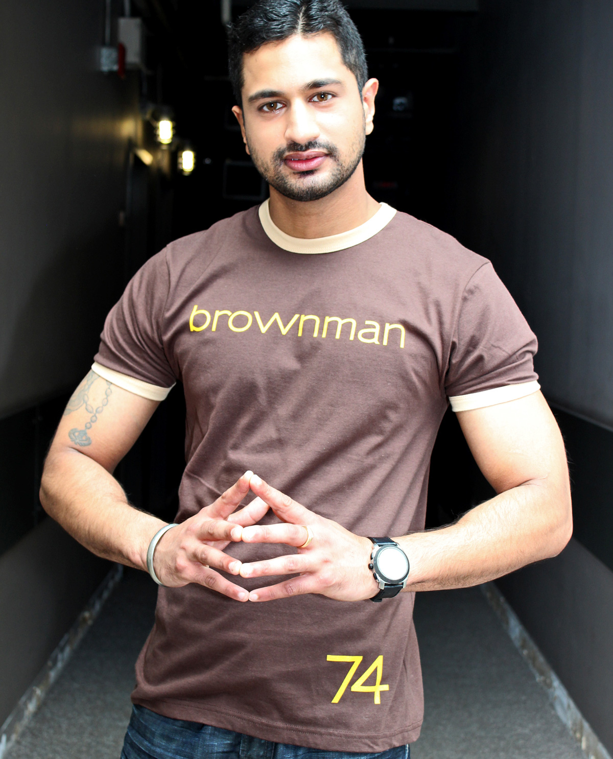 South Asian Male Model wearing American Apparel Brown Ringer T Shirt Graphic Design T.shirt with brownman74 graphic design on front.