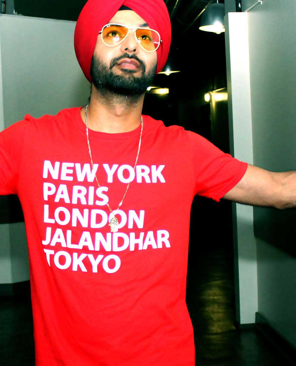 South Asian male wearing red fitted graphic design t.shirt with famous cities listed on front