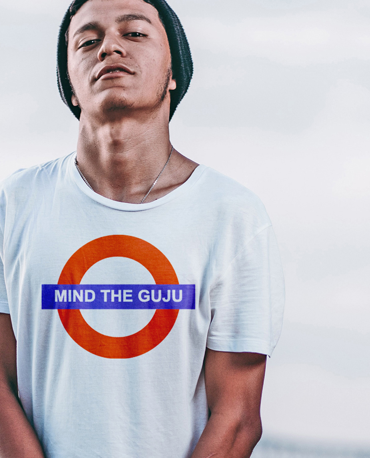 South Asian male model wearing white tshirt with graphic design print on front that says Mind The Guju